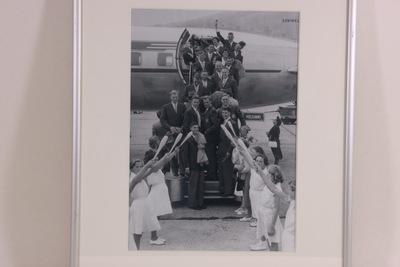 Een zwart-wit foto van de Nederlandse ploeg van de Olympische Zomerspelen 1952 Helsinki. De ploeg staat op de trap van het vliegtuig. Rechts onder het vliegtuig hangt een bordje met de inscriptie 'HELSINKI'.