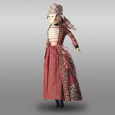 Tot ongeveer 1800 was Hindeloopen een welvarend Fries stadje. De dracht van de bewoners was totaal verschillend van de dracht van de rest van Friesland. Zelfs de taal was anders. Dit achttiende-eeuwse popje is aangekleed als ongehuwde vrouw. Ze draagt een gesteven en gevouwen hoofddoek, zonder daaronder het cilindervormige hoedje van de getrouwde vrouw. De lange overmantel (het wentke) was typerend voor de zondagse dracht van Hindeloopen. Vanaf 1750 gebruikte men voor de wentkes graag sits, een handbeschilderde stof uit India, in plaats van de daarvoor gebruikelijke stoffen. Het geruite katoen van de hoofddoek, de schort en de borstlap (de foarpeldoek) komt ook uit India.