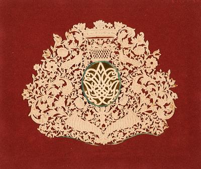 Dit knipsel is symmetrisch gesneden en verbeeldt blad- en bloemornamenten die uit hoornen van overvloed groeien, pauwen en een putto. In het midden staat een spiegelmonogram op goudpapier met erboven een kroon.
