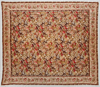 De doorgestikte deken heeft aan de bovenzijde twee soorten bedrukte katoen. Ze heeft een middenveld met een patroon van rozen in diverse kleuren op een bruin fond. Rondom is een bedrukte bloemenrand genaaid, met rozerode bloemen en groene blaadjes op een beige ondergrond, met aan weerszijden een randje met rood-witte nopjes.