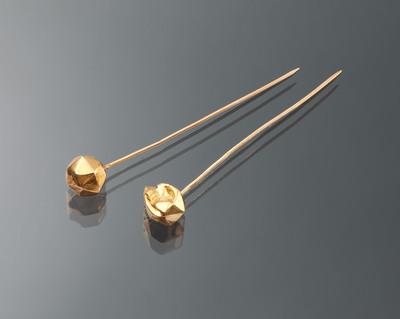 Deze 14-karaats gouden mutsenspelden zijn gedragen in Huizen en werden gebruikt om de muts aan het oorijzer vast te steken. Dergelijke 'facetspelden' werden bij diverse streekdrachten in Nederland gedragen.