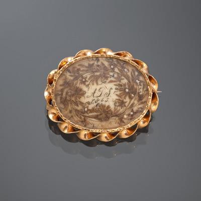 Broches met haarwerk werden als aandenken aan een persoon gedragen. Deze 14-karaats gouden broche draagt de initialen 'A.D.S.' en het jaartal 1865. Het meester- en gehalteteken zijn onleesbaar.
