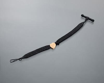 Deze horlogeketting heeft een gevlochten katoenen band met een gouden schuifje. Dergelijke horlogekettingen werden tussen 1880 en 1920 algemeen in Nederland gedragen. Dit exemplaar komt uit Terborg in de IJsselstreek. De vervaardiger is onbekend.
