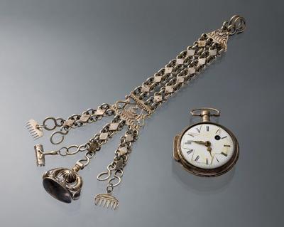 Op de afbeelding staat een horloge met een horlogeketting. Zowel de horlogekast als de ketting zijn van zilver. Het geheel is gedragen in het dorp Aagtekerke op het eiland Walcheren. Aan de horlogeketting hangen een signet (zegelstempel) en een paar miniatuurtjes: twee kammen en een roskam. De maker is onbekend.