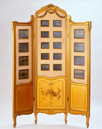Verguld houten drieslags kamerscherm, genre Louis XVI. In de schermen zijn autochroomplaten gemonteerd met afbeeldingen van bloeiende tulpen in de tuin van het Neues Palais te Potsdam. De middenslag bevat tien autochroomplaten van 9 x 12 cm, de zijslagen bevatten elk vier platen van 13 x 18 cm. Een meubel dat niet zou misstaan in de rijk van foto's voorziene zitkamer van koningin Emma is dit drieslags kamerscherm in Louis XVI-stijl. Hoewel het een aartrekkelijk meubel is dat zich zeer leent om te worden tentoongesteld, wordt het bewaard in een donker depot. De reden hiervan is de bijzondere inhoud van het scherm: de 18 autochroomplaten. De autochroom is een van de vroegste praktisch toepasbare kleurenprocédés in de fotografie. De techniek werd ontwikkeld door de gebroeders Lumière, die het vanaf 1907 op de markt brachten. Autochromes zijn in feite zwart-wit positieven (dia's) die, tegen het licht gehouden, zich vertonen als kleurenopnames. Het was een primitieve manier om tot een kleurenopname te komen en de kleurweergave van autochroomplaten is ook niet levensecht, maar wel wonderschoon. Omdat het bovendien de eerste methode was om in één belichting tot een kleurenbeeld te komen, werd de autochroom meteen een groot succes. Een groot nadeel van de autochroomplaat was wel dat de lichtgevoeligheid erg laag was. Daardoor was deze niet geschikt voor bewegende onderwerpen. Het stilleven was daarentegen wel een geliefd genre, vooral het bloemstilleven was erg populair, maar ook ondergaande zonnen vormden een populair thema. Het kamerscherm werd in 1915 door de Duitse keizer Wilhelm II cadeau gedaan aan koningin Wilhelmina. Het was op aanwijzing van keizerin Auguste-Viktoria (1858-1921) vervaardigd en was een tegengeschenk. Twee jaar eerder had Wilhelmina de keizer heesters en een grote partij tulpenbollen cadeau gedaan, bestemd voor het park Sancoussi en het Neue Palais te Potsdam. De autochroomplaten in het scherm zijn - hoe toepasselijk - opnames van deze tulpen. De opn