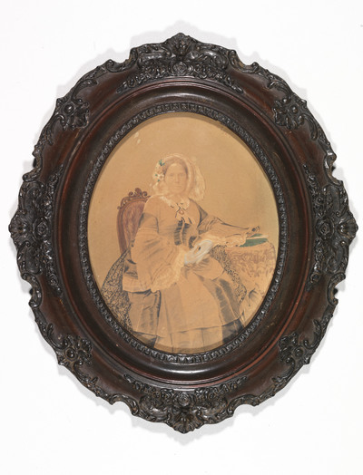 Een van de vroegste foto's in de collectie fotografie van Paleis Het Loo is dit portret van prinses Marianne (1810-1883) uit ca. 1855. Het betreft een zoutdruk. Wat direct in het oog springt, is dat het een foto in kleur is. Dat wil zeggen, de kleur en een deel van de detaillering zijn door de fotograaf achteraf handmatig aan het oorspronkelijk monochrome beeld toegevoegd. Daarvoor gebruikte hij penseel en waterverf. Hoewel de fotografie meteen vanaf haar ontdekking in 1839 alom werd geprezen om haar ongekend natuurgetrouwe weergave van de werkelijkheid, werd het ontbreken van kleur direct als grote tekortkoming ervaren. Al gauw werd gezocht naar manieren om wel rechtstreeks tot een kleurenbeeld te komen. Tot die tijd werd soms, zoals hier, kleur handmatig aangebracht. Nog een reden om het beeld achteraf te bewerken was dat een zoutdruk een relatief weinig gedetailleerd, enigszins onscherp fotografisch beeld oplevert. Het primitieve karakter van de vroege fotografie komt ook tot uitdrukking in de wat houterige pose van de prinses. De eerste foto-emulsies waren relatief weinig lichtgevoelig, waardoor er vaak lang moest worden belicht. Om bewegingsonscherpte te voorkomen werd de posant zoveel mogelijk gefixeerd. Met de linkerarm rustend op een tafeltje naast haar, de rechterarm half gebogen langs haar lichaam omlaag, maar zo dat ze de handen ineen kan vouwen, zit de prinses tussen stoel en tafel ingeklemd en vormt zo een compacte eenheid met deze meubelstukken. Het ovale lijstje onttrekt het meest massieve deel van de foto (de onderkant van de wijd uitlopende rok en het kleedje dat over het tafeltje hangt) aan het zicht, waardoor er een enigszins statische, doch elegante pose overblijft. De zoutdruk, die de basis vormt van deze voorstelling, is in de loop der tijd dusdanig vervaagd en het papier is zo vergeeld, dat het fotografische beeld vrijwel is verdwenen. Als een van de oudste foto's in de verzameling, als zoutdruk en als zeldzaam fotografisch portret van Prinses