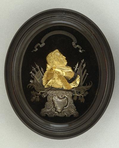 Reliëfportret van Willem IV, prins van Oranje-Nassau, waarbij het portret is uitgevoerd in goud, met decoraties en ornamenten in zilver. De arm van het door de prins gedragen harnas eindigt in een gestileerde leeuwenkop en de prins draagt een zwart gelakte sjerp. Links van het portret zijn twee speren met vaandels, één losse speer, een trompet en een vulschep (om buskruit af te meten) afgebeeld, met daaronder een kanonsloop. Rechts van het portret zien we één speer met vaandel, losse speren een, geweerloop en een pompstok of baton. Het reliëfje is gemonteerd op zwart fluweel en laat de prins van terzijde zien. Het borststuk staat op een zilveren sokkel met asymmetrische schelpmotieven, waarin de naam van de prins en het jaartal 1748 staan gegraveerd. In de banderol boven het hoofd van de prins staat het opschrift: IN SPEM CONCORDIAE PACISQUE VENIT ET UTRAQUE ADEST ('Hij is gekomen in de hoop op eendracht en vrede en beide zijn daar'). Prins Willem IV overleed in 1751, nadat hij slechts vier jaar daarvoor benoemd was tot erfstadhouder van de Verenigde Provinciën en opperbevelhebber over leger en vloot. Een goede reputatie heeft hij echter niet in de geschiedenis, want grote daden heeft hij niet verricht. Toch is er een reden waarom we prins Willem IV ook vandaag nog in herinnering zouden moeten houden. Hij was onze prins van het rococo. Gezegend met een verfijnde smaak, een uitstekende opvoeding en een ruime beurs legde hij de grondslag voor de rijke verzamelingen schilderijen, antiquiteiten, ethnografica, boeken, munten en penningen, die na de Franse tijd rijkseigendom zouden worden en die de basis vormen van openbare collecties als het Mauritshuis, het Rijksmuseum, de Koninklijke Bibliotheek en het Geldmuseum. Hij gaf de Italiaanse beeldhouwer Agostino Carlini opdracht uitbundig rococo-meubilair te ontwerpen voor de Oranjezaal in Huis ten Bosch en stuurde zijn hofarchitect Pieter de Swart naar Parijs om daar de laatste nieuwtjes op het gebied van de bouwkunst te le