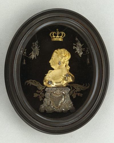Reliëfportret van Anna van Hannover, prinses van Oranje-Nassau, waarbij het portret is uitgevoerd in goud, met decoraties en ornamenten in zilver. Het reliëfje is gemonteerd op zwart fluweel en laat de prinses van terzijde zien. Het borststuk staat op een zilveren sokkel met asymmetrische schelpmotieven, waarin de naam van de prinses en het jaartal 1748 staan gegraveerd. Anna's portret, dat met drie diamantjes is bezet, draagt een vergulde koningskroon -een verwijzing naar haar voorname afstamming als oudste dochter van koning George II van Engeland- en is omringd met muziekinstrumenten en palm- en Oranjetakken. Van deze reliëfportretjes zijn thans vier sets bekend. Uit de herkomst hiervan blijkt dat zij door de prins aan vrienden en vertrouwelingen zijn gegeven als dank voor bewezen diensten. Prins Willem IV overleed in 1751, nadat hij slechts vier jaar daarvoor benoemd was tot erfstadhouder van de Verenigde Provinciën en opperbevelhebber over leger en vloot. Een goede reputatie heeft hij echter niet in de geschiedenis, want grote daden heeft hij niet verricht. Toch is er een reden waarom we prins Willem IV ook vandaag nog in herinnering zouden moeten houden. Hij was onze prins van het rococo. Gezegend met een verfijnde smaak, een uitstekende opvoeding en een ruime beurs legde hij de grondslag voor de rijke verzamelingen schilderijen, antiquiteiten, ethnografica, boeken, munten en penningen, die na de Franse tijd rijkseigendom zouden worden en die de basis vormen van openbare collecties als het Mauritshuis, het Rijksmuseum, de Koninklijke Bibliotheek en het Geldmuseum. Hij gaf de Italiaanse beeldhouwer Agostino Carlini opdracht uitbundig rococo-meubilair te ontwerpen voor de Oranjezaal in Huis ten Bosch en stuurde zijn hofarchitect Pieter de Swart naar Parijs om daar de laatste nieuwtjes op het gebied van de bouwkunst te leren. Zijn plannen om een nieuw en modern paleis in Den Haag te laten verrijzen, zijn door zijn voortijdige dood op niets uitgelopen. De gouden p