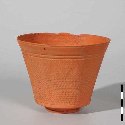 Beker van zeer fijn gladwandig Nijmeegs-Holdeurns aardewerk, zeer dun en scherp gevormd uit de Romeinse tijd. Holwerda type 11. De kantharosachtige beker (zonder oren) op een standring heeft een zeer rechte schuinuitstaande wand en rechte rand. De wand is voorzien van een gearceerde versiering, bovenaan afgesloten door twee groeven. De beker is gevonden in het grafveld ten westen van de Museum Kamstraat in Nijmegen.