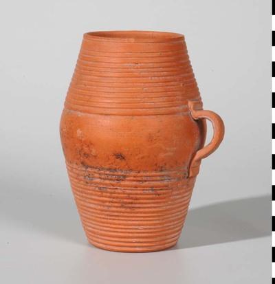 Tonvormige beker van fijn Nijmeegs-Holdeurns aardewerk. Onderaan en bovenaan een brede baan van rondomlopende groeven. Rondgebogen oor, dat even boven de knik is aangezet. Holwerda type 20a. De beker dateert uit de Romeinse tijd en is gevonden aan de oostzijde van de Museum Kamstraat in Nijmegen.
