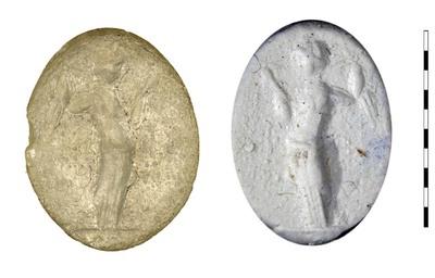 Gem, gesneden imitatie van chalcedoon, uit de Romeinse Republikeinse-vroegkeizerlijke periode. Afgebeeld is de godin Aphrodite (Venus), gekleed in een lange chiton, met een spiegel in haar linkerhand. Ze is bezig het haar, dat over haar rechter schouder hangt, met haar rechterhand glad te trekken. Ze is frontaal afgebeeld met haar hoofd naar rechts.
