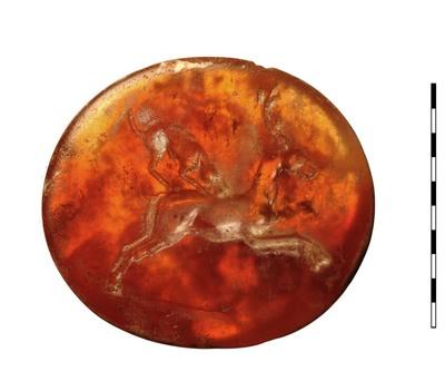 Gem, gesneden steen (karneool), uit de vroeg Romeinse periode. Afgebeeld is een springend hert met een hond die op zijn rug is gesprongen, wellicht om het hert neer te halen. Er is een grondlijn zichtbaar.