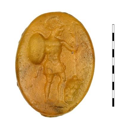 Gem, gesneden imitatie van sarder, uit de Romeinse Republikeinse periode. Afgebeeld is een soldaat, naar rechts gericht, met een kuras aan en een helm op, die een speer in zijn linkerhand heeft en een schild in zijn rechterhand. Aan zijn voeten nog een kuras. De soldaat heetf blote voeten. Hij is driekwart frontaal afgebeeld en zijn hoofd naar rechts gebogen. Een korte grondlijn is weergegeven.