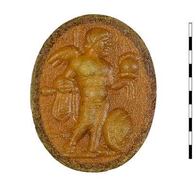 Gem, gesneden imitatie van sarder, uit de Romeinse Republikeinse-vroegkeizerlijke periode. Afgebeeld is Eros (Cupido) houdt een helm in zijn linkerhand en in zijn rechterhand een speer. Zijn himation is gedrapeerd over zijn rechterarm. Aan zijn voeten staat een rond schild. Houding is driekwart frontaal en het hoofd naar rechts. Er is een grondlijn.