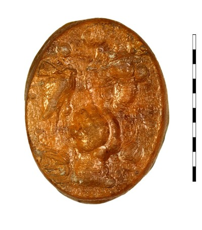 Gem, gesneden imitatie van karneool, uit de Romeinse Republikeinse tijd. Frontaal afgebeeld is een hand (volgens van Buchem kop/hoofd) met symbolen: papavers, hoorn des overvloeds en vogel (kraanvogel of reiger). Deze combinatie van symbolen is tamelijk veel voorkomend in deze periode.