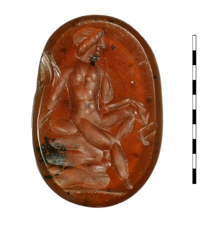 Gem, van natuursteen (karneool), uit de Romeinse periode. Afgebeeld is Mercurius (Hermes),driekwart frontaal kijkend naar rechts, naakt en gezeten op een rots in een ontspannen houding. Zijn linkerarm rust op zijn knie en hij houdt een caduceus in zijn linker hand. Hij ondersteunt zichzelf met zijn andere hand. Zijn haar is rond zijn hoofd gedrapeerd in een wrong. Er is een grondlijn zichtbaar.