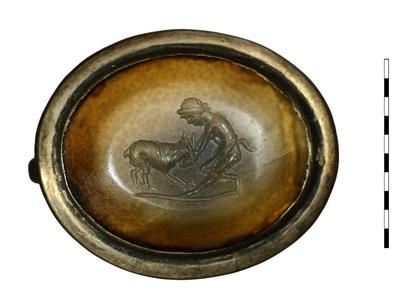 Gem, van natuursteen (chalcedoon) uit de Romeinse periode. Afgebeeld is Paniscus, naar links gedraaid, die de kop van een geit in beide handen houdt. Er is een grondlijn zichtbaar.