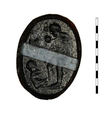 Gem, een gesneden imitatie van gestreepte agaat, uit de Romeins-Republikeinse periode (Etruskisch-Italische stijl). Afgebeeld is een man, gekleed in een korte mantel van dierenhuid. Hij buigt zich naar links naar een klein, naakt kind aan zijn voeten. Thema veel voorkomend, wellicht te identificeren als het vinden van Oidipous.