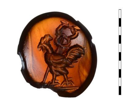 Gem, van natuursteen (karneool), uit de Romeinse periode. Afgebeeld is een haan, naar links wandelend; de caduceus is diagonaal achter het dier afgebeeld. Er is een grondlijn zichtbaar.