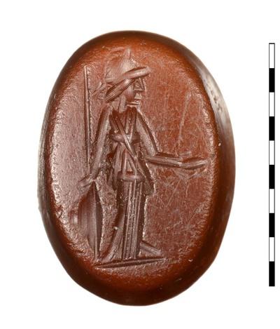 Gem van natuursteen (sarder) uit de Romeinse periode. Afgebeeld is een staande Minerva, frontaal met het gezicht naar rechts. Ze draagt een helm met helmbos en een peplos met grote overhangende plooi. Ze heeft een speer in haar rechterhand en ook staat rechts een schild op de grond. In haar andere hand heeft ze een patera. Er is een grondlijn zichtbaar.