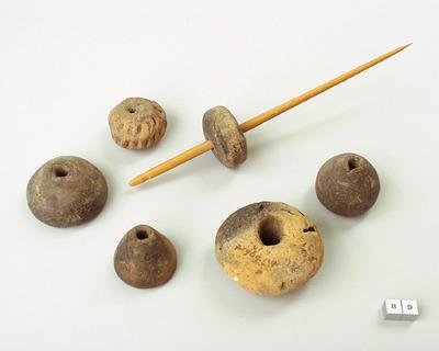 Afgeplat konisch spinklos van aardewerk uit de ijzertijd.