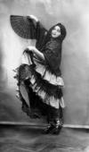 Ritratto della danzatrice Olga Reich, mentre esegue un passo di danza con un costume spagnolo