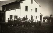 Scolaresca ritratta davanti ad una scuola elementare, in campagna. In mezzo ai bambini compare una maestra