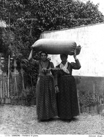 Two women bearing wheat on their heads in San Remo.