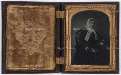 portrait en buste et en studio d'une femme assise avec un livre en main