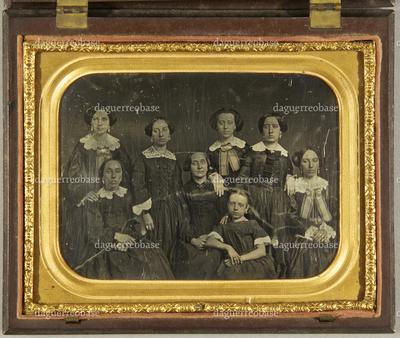 Gruppenbild mit 7 Frauen und einem Mädchen, sitzend und stehend. Alle Frauen in dunklen Kleidern mit weißen Kragen, drei tragen die gleiche gestreifte Halsschleife, Dreiviertelfigur.