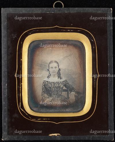 Portrett av pike i mønstret kjole med sløyfe i håret sittende på stol med armen lenende på et bord.   Portrait of girl in patterned dress with ribbons in hair, sitting on chair, arm leaning on table.