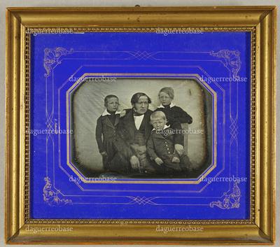 Vater mit seinen drei kleinen Söhnen vor einem gespannten Tuch sitzend. Zwei Jungs stehen hinter ihm, den Jüngsten hält er im Arm, Halbfigur.