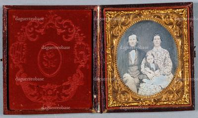 Portrait of a family, a man and a woman and a small child. Puolikuvassa perhe, mies, nainen ja pieni tyttö.  Tyttö istuu naisen sylissä. Naisella on yllään lehväkuvioinen mekko, miehellä puku, kuvioitu liivi ja ruutuhousut.