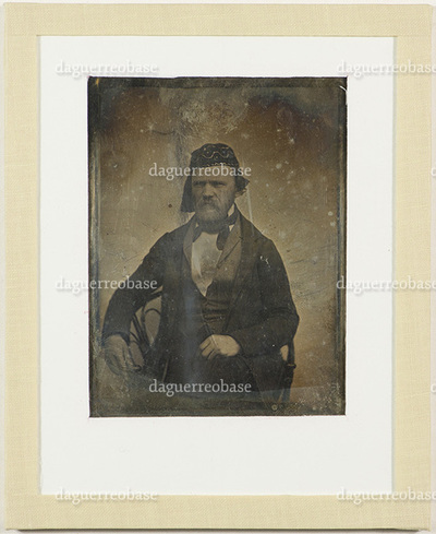 Portrait of photographer Hans Krum (15.02.1818 - 03.10.1882). A bearded man with headwear sitting on a chair.