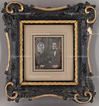 Portrait of a middle-aged couple. Muotokuvassa istuu mies ja nainen. Naisella on vaalea pitsimyssy päässä.