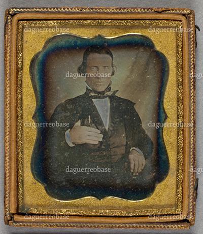 Portrait of a man. Puolikuva miehestä, joka riiputtaa kättään peukalo liivin kainaloaukossa, rintataskusta pilkottaa kynä.