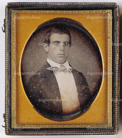 Portrait of a young man. Rintakuvassa nuori mies. Miehellä on yllään tumma takki, vaalea paita ja kaulassa solmuke.