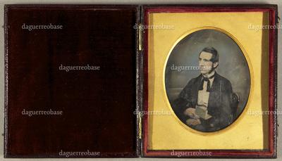 Junger Mann mit Backenbart, ein aufgeschlagenes Buch in der Hand, seitlich vor einem Wolkenhintergrund sitzend, Halbfigur, koloriert.