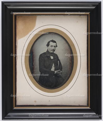 portrait de 3/4 d'un homme assis en studio tenant un livre sous le bras