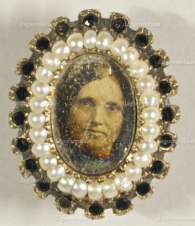 Bildnis einer Frau umrahmt von einem Perlenkranz in einem Manschettenknopf oder Reversknopf.