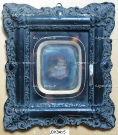 Rektangulær daguerreotypi i mørk indramning med rundede hjørner og guld ornamentik. I sort træramme udsmykket med gips-stukatur. Sortmalet. Motiv: Torso af o. 10-årig pige, der holder en bold i hånden.