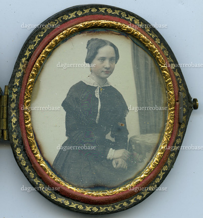 Portrait of an unknown young woman, sitting in a chair, near a round table with a tablecloth; wearing a dark dress with a fine lace collar; in front of neutral background; on the right side, behind the table, is a part of a curtain visible; applied color