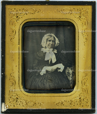 Portrait of an unknown elderly woman, sitting in a chair near a table with tablecloth; in a black dress with white lace collar and lace bonnet; against a dark neutral background (curtain)