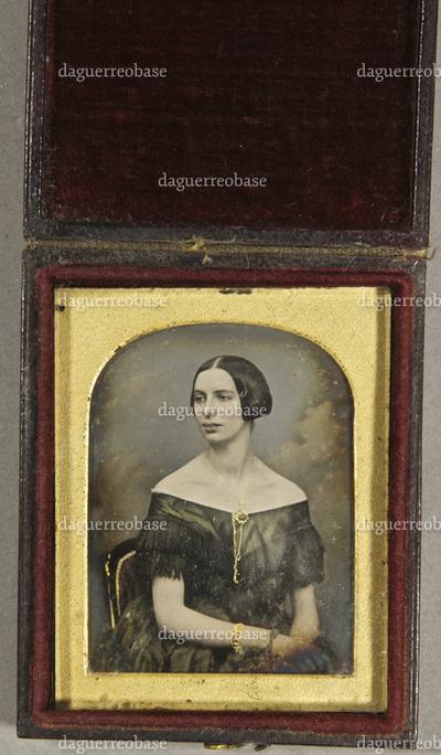 Junge Frau in schulterfreiem Kleid trägt eine Halskette und ein Armband, zur Seite aus dem Bild blickend, vor einem Wolkenhintergrund sitzend, Halbfigur, koloriert.