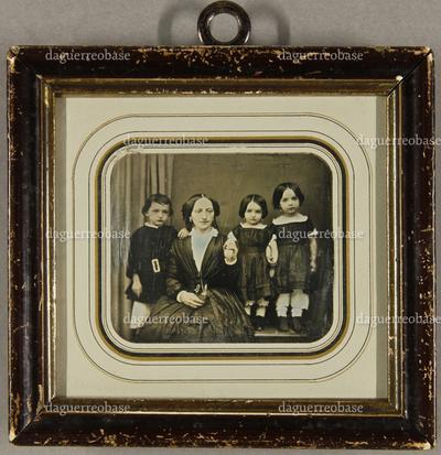 Mutter mit ihren drei Kindern. Der Sohn steht rechts von ihr, die beiden kleinen Töchter stehen auf der anderen Seite neben ihr auf einem Stuhl, Dreiviertel- und Ganzfigur.