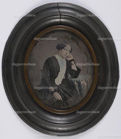 portrait en studio et en buste d'une jeune femme assise accoudée à une table