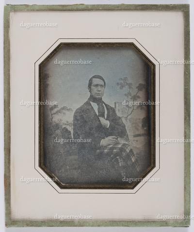 portrait en buste d'un homme assis, la main dans son manteau