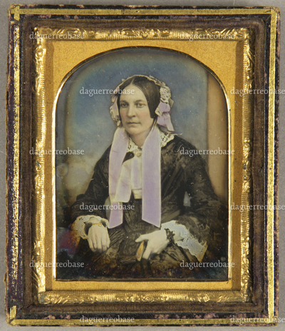Ältere Frau mit weißer Haube und weißer Halsschleife, vor Wolkenhintergrund sitzend, Knieportrait, koloriert.