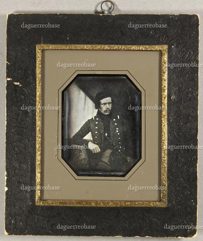 Mann mit einer Kappe und Uniformjacke, einen Stock in einer Hand haltend, der andere Arm ruht auf einem Tisch, seitlich aus dem Bild blickend, Halbfigur.