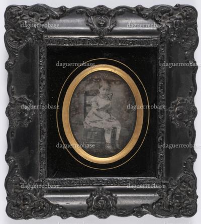 portrait en pied et de 3/4 profil d'un garçon assis en studio